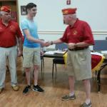 Dakota Hemberger being presented with Scholarship by Commandant Joe Johnston.  Father Dennis Hemberger looking on
