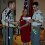 Scout Master Bill Poteet presenting son, Christopher, with Eagle Scout Certificate while Mother, Cheryl, looks on.